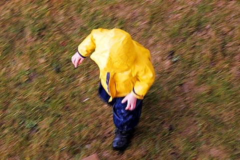Running kid with yellow rain jacket, from the top