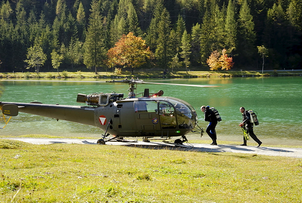 Members of rescue team in diving suits ready to mount helicopter to participate in rescue exercise at lake Pillersee, Tyrol Austria