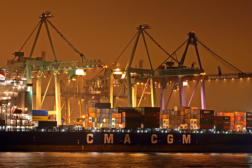 Container ship lying at container terminal Burchardkai in Hamburg harbour at river Elbe in the night - Germany, Europe