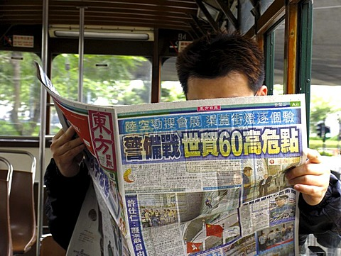 Reading man in tramway, Hongkong, China, Asia