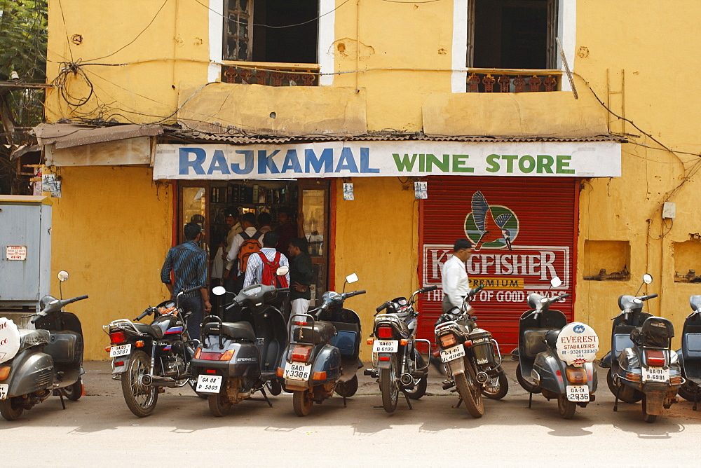 A row of men at a wine store in a street of Panaji or Panjim, Goa, India