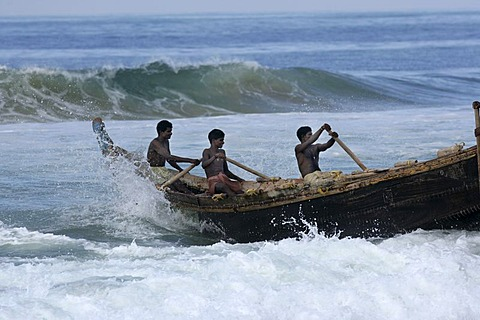 |IND, India, Kerala, Trivandrum : Fishermen at the beach, Malabar coast, south of Trivandrum. Rowing a wooden fishing boat through the surf into the open water. |