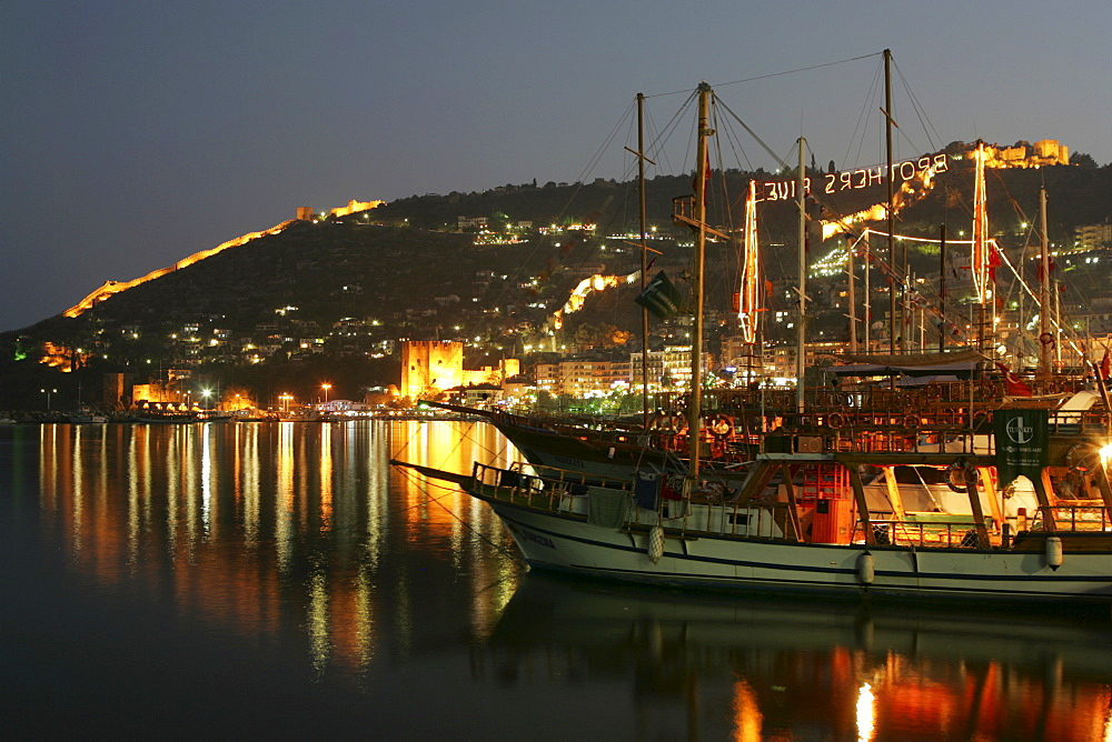 TUR, Turkey, Alanya : Turkish Riviera. Harbour at night, sailing boats for tourists, citadell, tower Kizil Kule . |