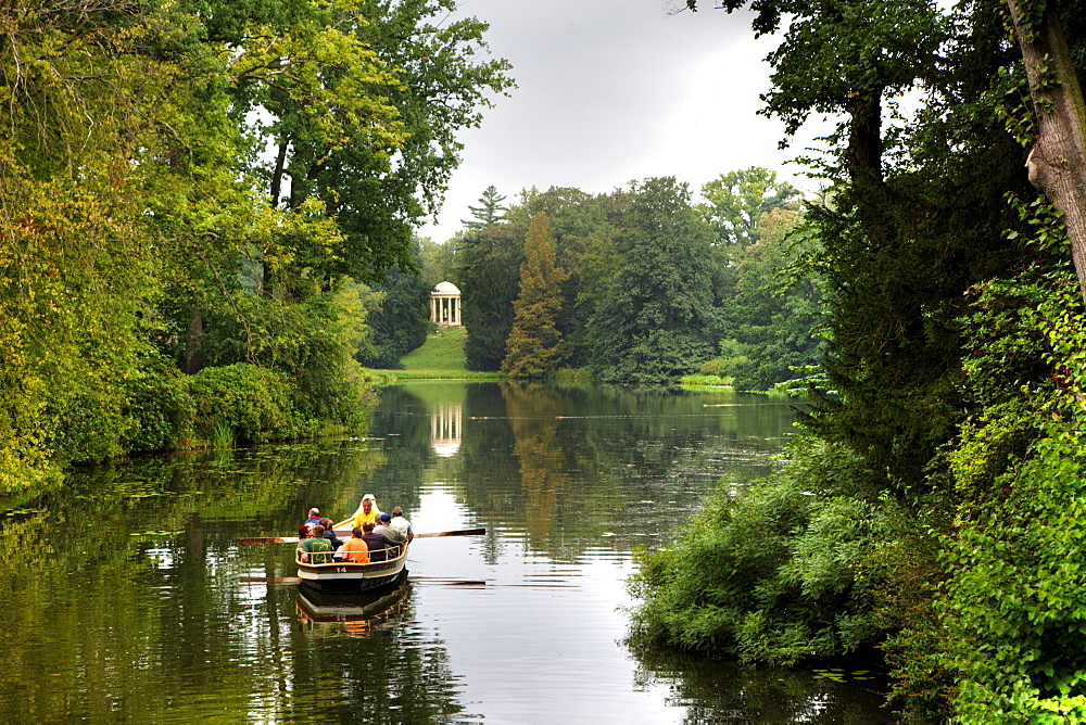 Rowboat going across the lakes and canals at Schoch's Garden, Kleines Walloch watercourse and the Venus Temple, Dessau-Woerlitz Garden Realm, UNESCO World Heritage Site, Dessau, Saxony-Anhalt, Germany