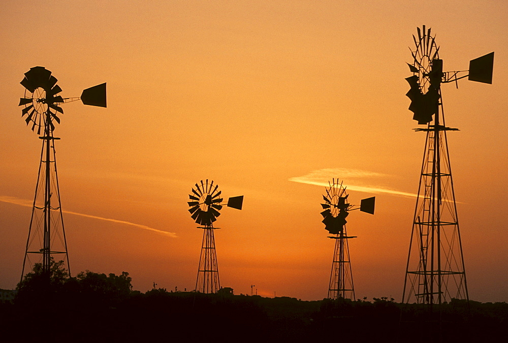 Wind driven water pumps silhouetted against evening sunset sky near Protaras, Cyprus