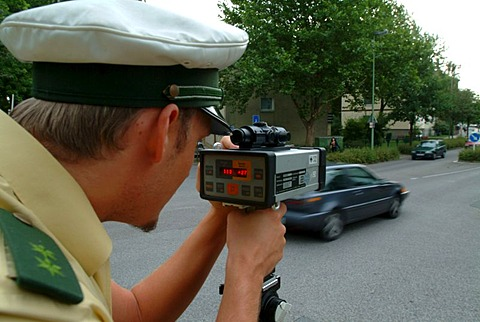 DEU, Germany, Essen: Traffic speed control in a speeding zone of 30 km/h near a school, with a laser measure gun. Daily police life. Officer from a city police station.