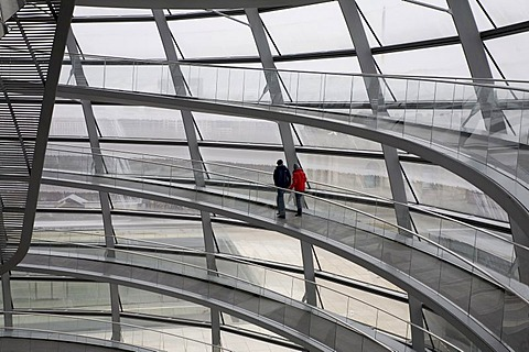 Couple walks hand in hand on a stairway in a huge modern cupola made of glass, Reichstag, Berlin Germany