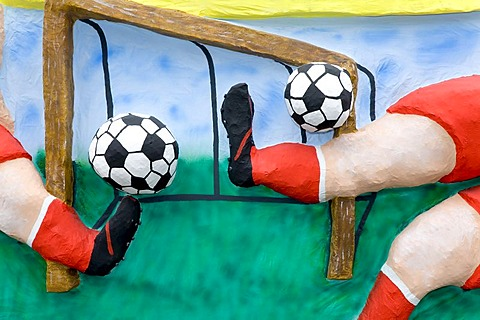 Two footballers are shooting simultaneously two balls, caricature made of paper mache , monday before lent parade, Duesseldorf, NRW, Germany