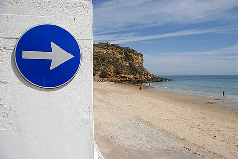 A street sign on a wall next to a beach in Salema, Algarve, Portugal