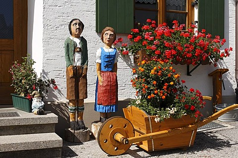 Wooden figures of a couple, wooden barrow in front of a farmhouse in Stoetten am Auerberg, interior view, Allgaeu, Swabia, Bavaria, Germany, Europe