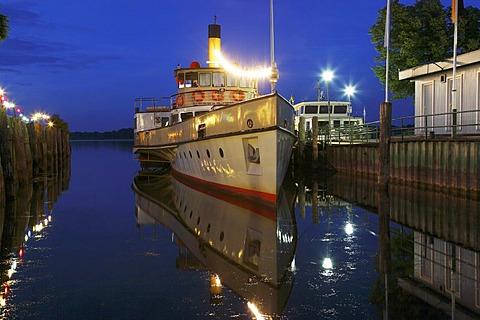 "Night-time illuminated pleasure paddle steamer ""Ludwig Fessler"" in Prien harbour, Lake Chiemsee, Chiemgau, Upper Bavaria, Germany, Europe"