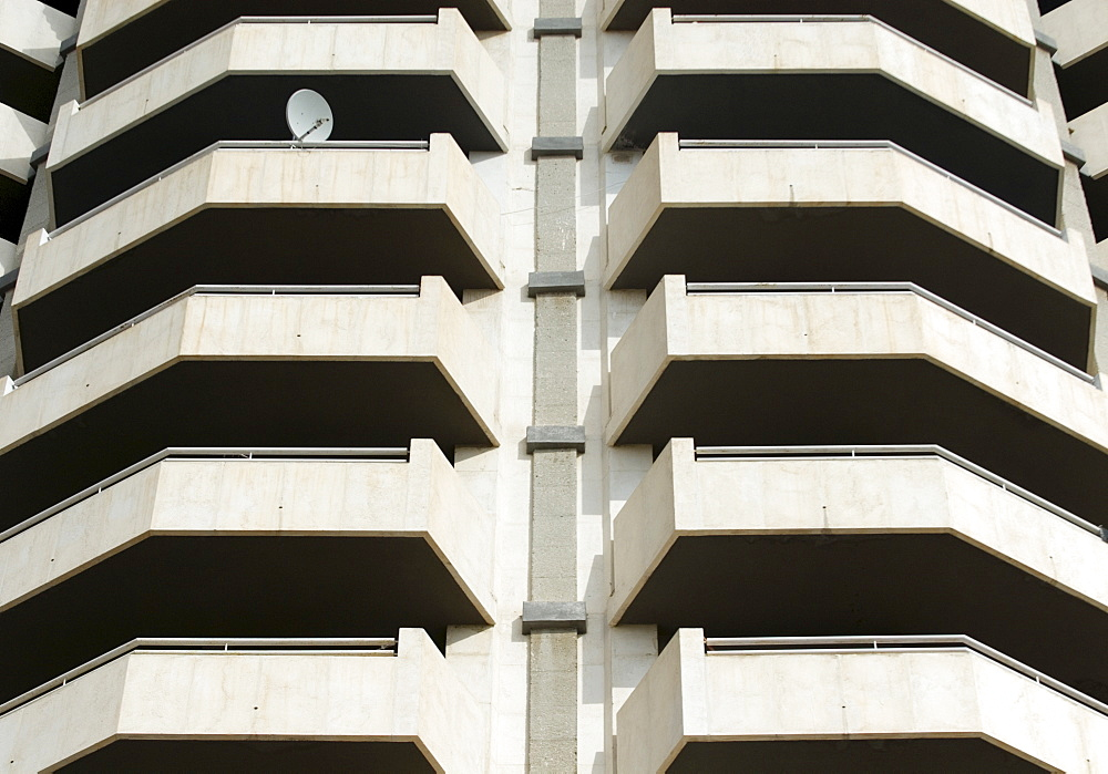 Satellite dish mounted to a balcony on a fortress-like high-rise apartment building in Benidorm, Alicante, Spain