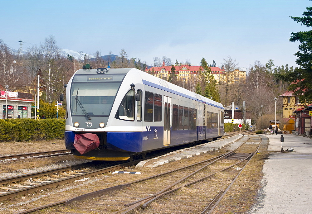 Electric Tatra train at the Tatranska Lomnica train station and the Grand Hotel Praha (back), Slovakia