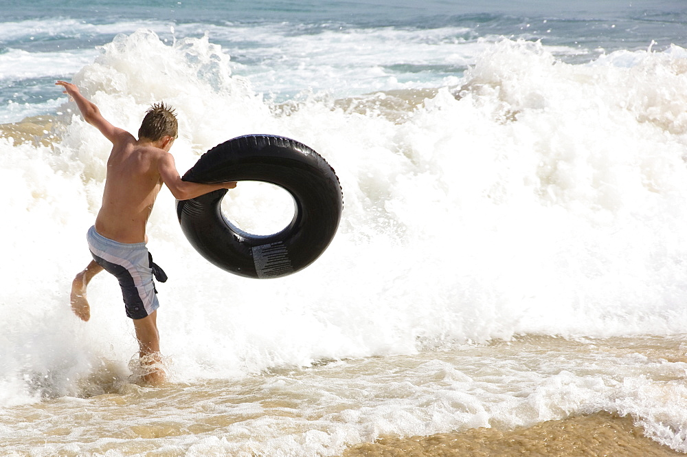 Teenager with floating tyre, Jandia, Fuerteventura, Canary Islands, Spain