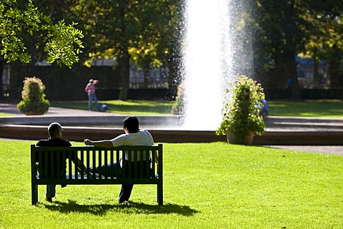 People in a park sitting on a bench in front of a fountain, Hesse, Germany
