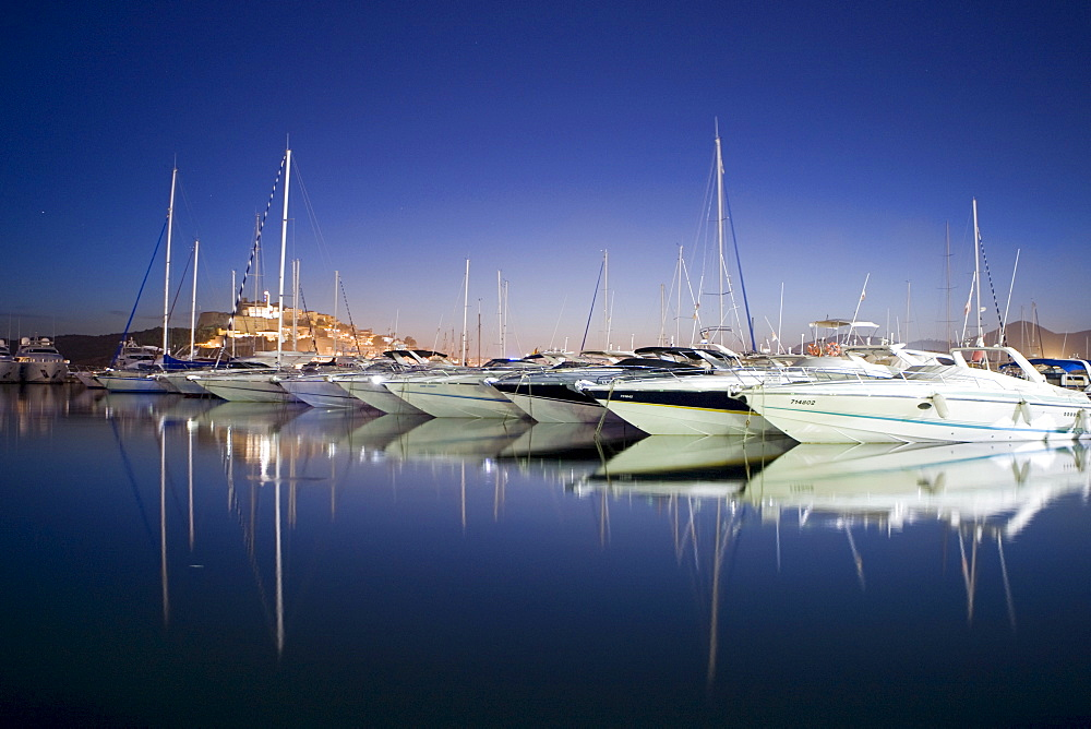 Yachts in the marina of Eivissa in front of the Dalt Vila at dusk, Ibiza, Baleares, Spain