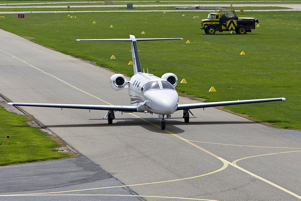 Small, twin-engined business jet taxiing on the runway of Mannheim Airport, Baden-Wuerttemberg, Germany, Europe