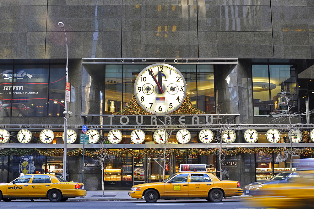 Midtown Manhattan, 5th Avenue. Tourneau clock store with many big clocks, showing the different times in the world, Corner 57th Street, New York, USA