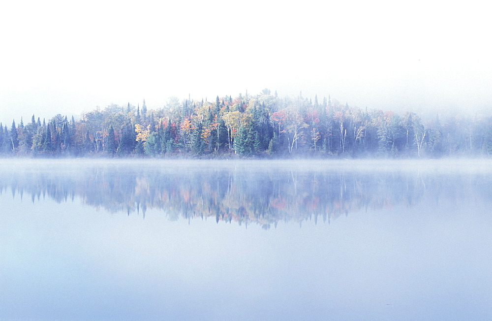 Early morning mist and autumn coloured trees on an island in Lac Bouchard Lake, La Mauricie National Park, Quebec, Eastern Canada