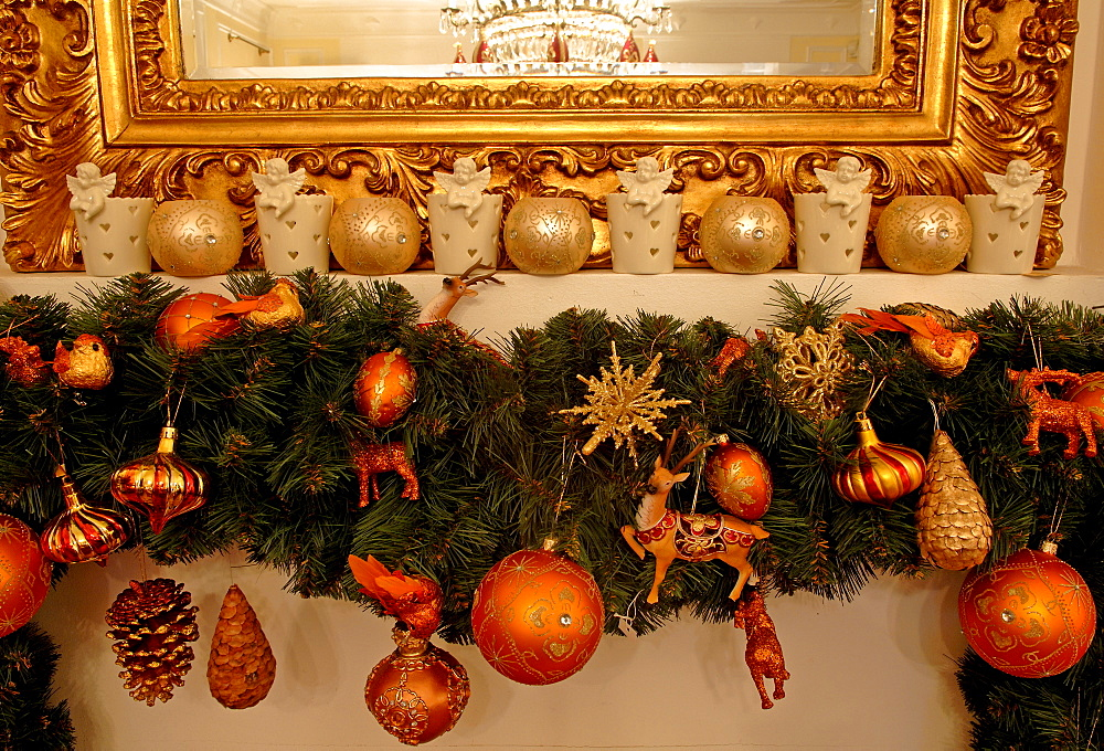 Mantelpiece showing edge of gold-framed mirror, Christmas ornaments hanging from pine sprigs from mantel