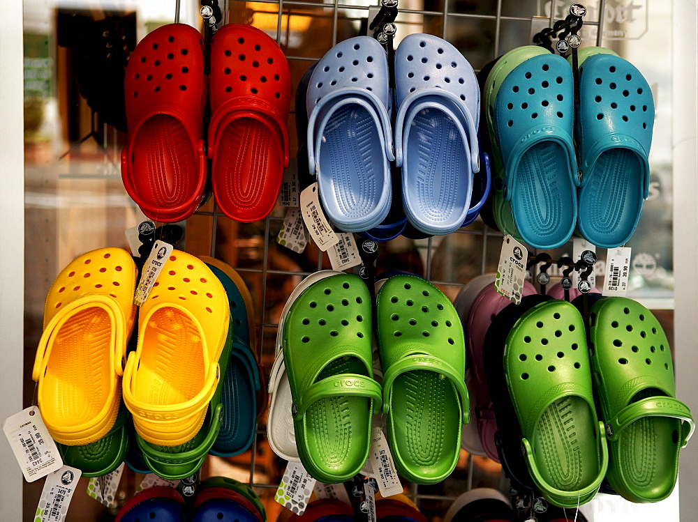 Brightly coloured plastic shoes on a grate, Lueneburg, Lower Saxony, Germany, Europe