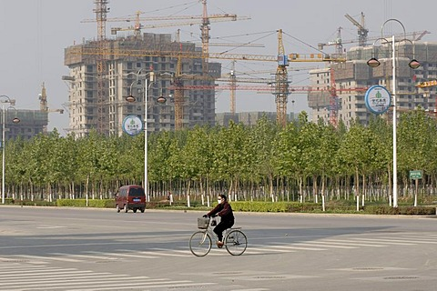 Bicyclist on a street, in the background multi-storey buildings under construction, Beijing, China