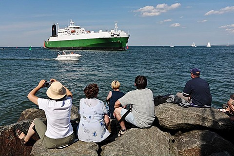People watching a cargo ship entering the Rostock Harbour, Warnemuende, Mecklenburg-Western Pomerania, Germany, Europe