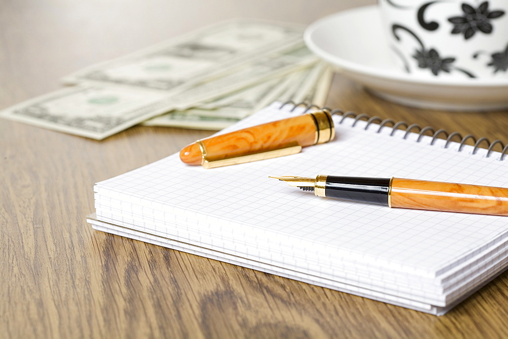 Fountain pen on a table with notebook, US cash and cup and saucer