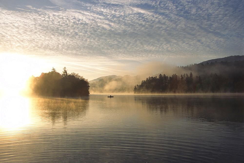 Fisherman on Reintalersee (Reintal Lake) at sunrise, North Tirol, Austria, Europe