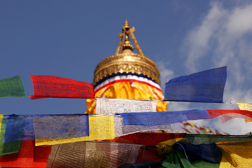 """Red, yellow, white, blue and green prayer flags at the Bodnath stupa, accompanied by traditional Tibetan prayer verses """"Om mani padme hum, """" which are said to be carried throughout the world by the wind, Kathmandu, Nepal, Asia"""