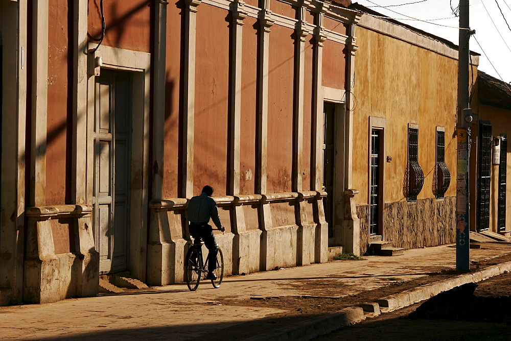 Person riding a bike on an empty pavement, sidewalk in Granada, Nicaragua, Central America
