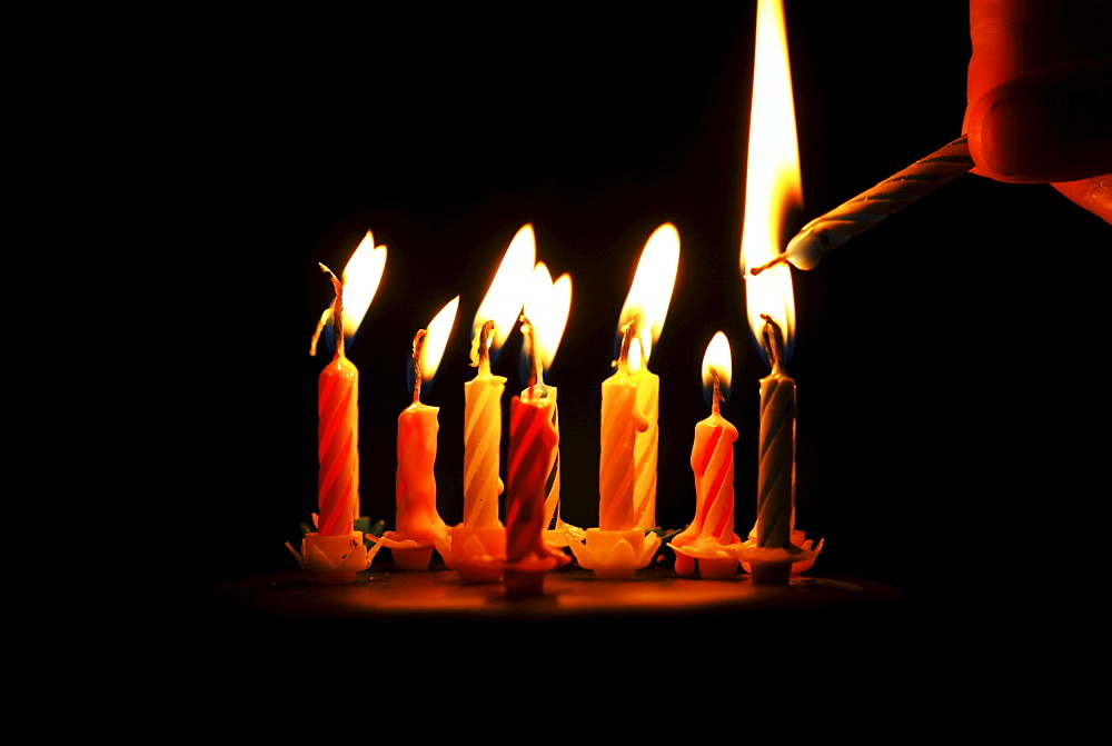 Lighting a candle on a birthday cake