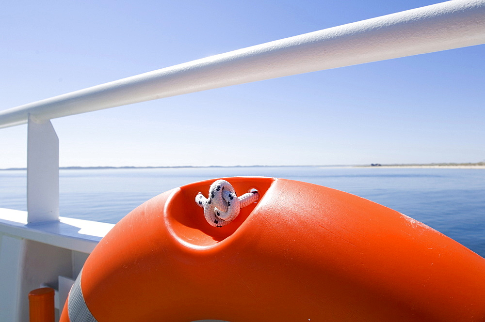 Detail of orange lifebelt on a white rail on a ferry in the North Sea.