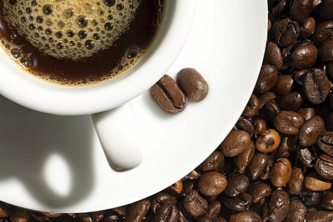 A cup of coffee near roasted coffee beans