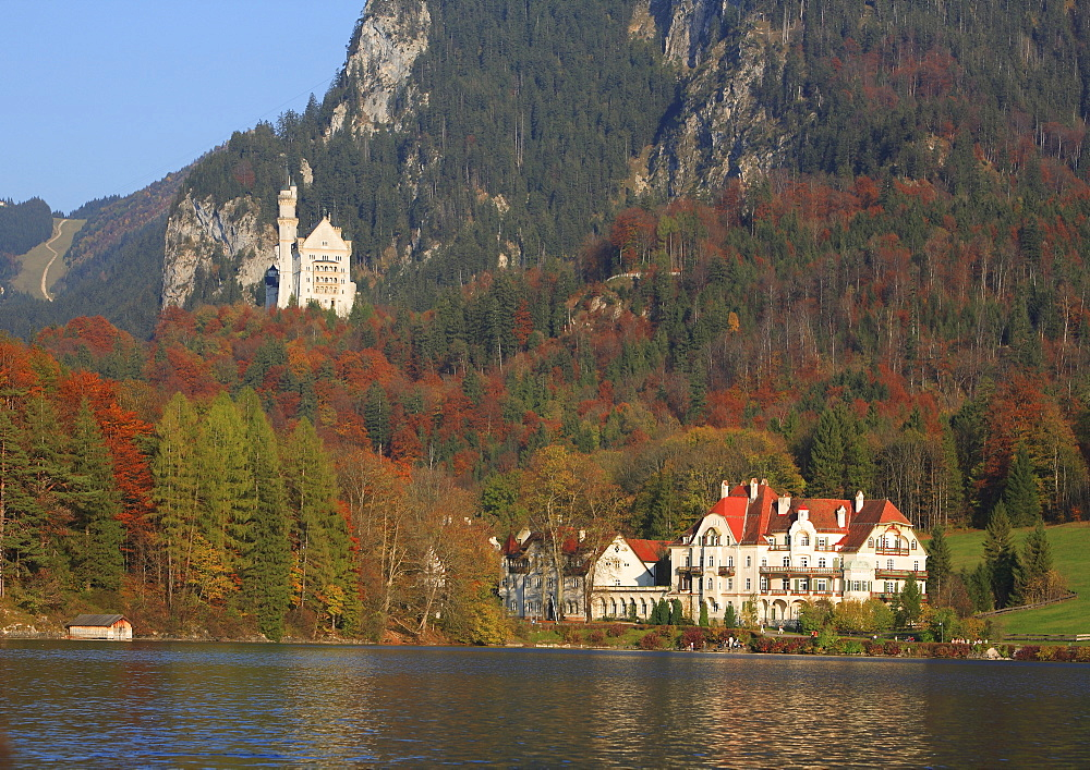 Alpsee lake, Haus Alpenrose and Neuschwanstein Castle in evening light, Schwangau near Fuessen, Bavaria, Germany