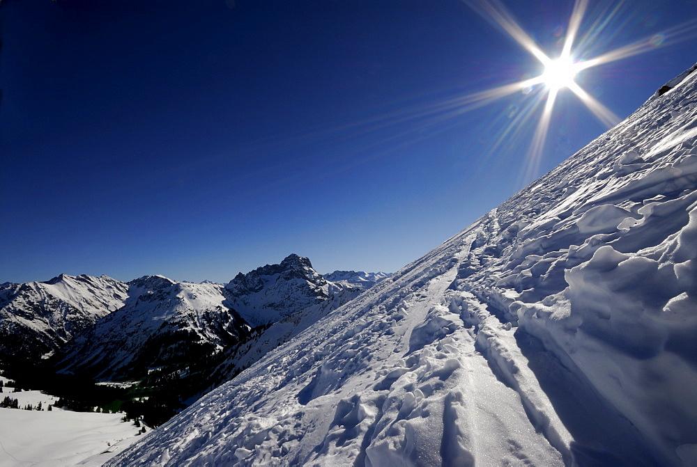 Steep slope (backlit) and a view of the Allgaeu Alps, Baad, Kleinwalsertal, Vorarlberg, Austria, Europe