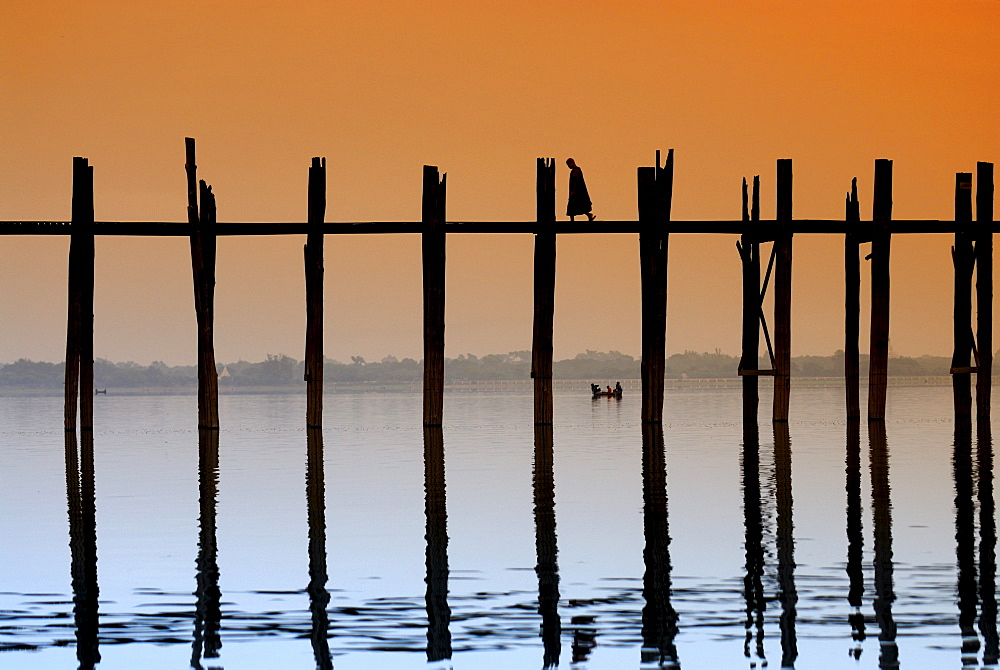 Monks crossing the U Bein Bridge at sunset, old wooden teak bridge, Mandalay, Myanmar, Southeast Asia