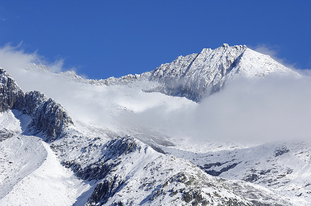 Clouds with snowy mountains in the Aletsch area, Goms, Valais, Switzerland