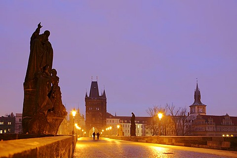 Two people walking over the Charles Bridge at dawn, Prague, Czech Republic