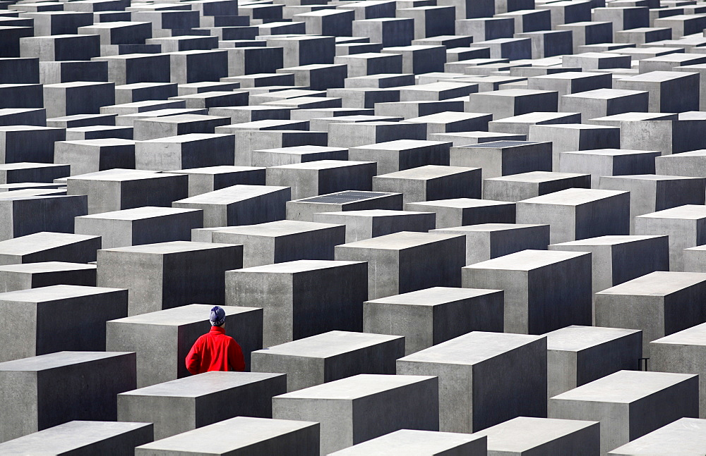 Person in red jacket walking amongst the concrete slabs of the Holocaust Memorial, Berlin, Germany