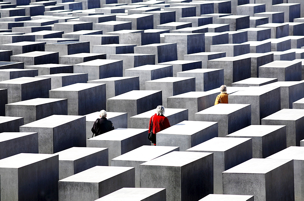 Three people dressed in red, black and yellow-gold jackets walk amongst concrete slabs of the Holocaust Memorial, Berlin, Germany