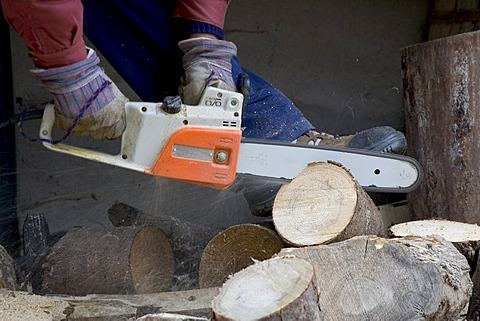 A man sawing pieces of wood with a chainsaw