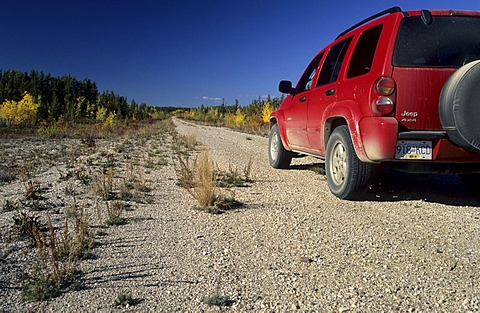 Red fourwheeldrive on a dirt road, Northwest Territories, Canada