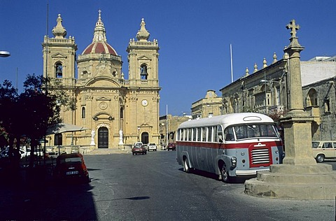 Old bus in front of the church of Nadur, Gozo Island, Malta