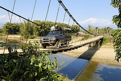 Fourwheeldrive vehicle driving over a suspension bridge, Kachin State, Myanmar