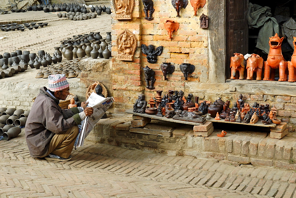 Man reading a newspaper in front of a souvenir shop, Bhaktapur, Nepal