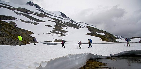 Hikers carrying backpacks crossing a snowy valley along the Chilkoot Trail, British Columbia, Canada, North America