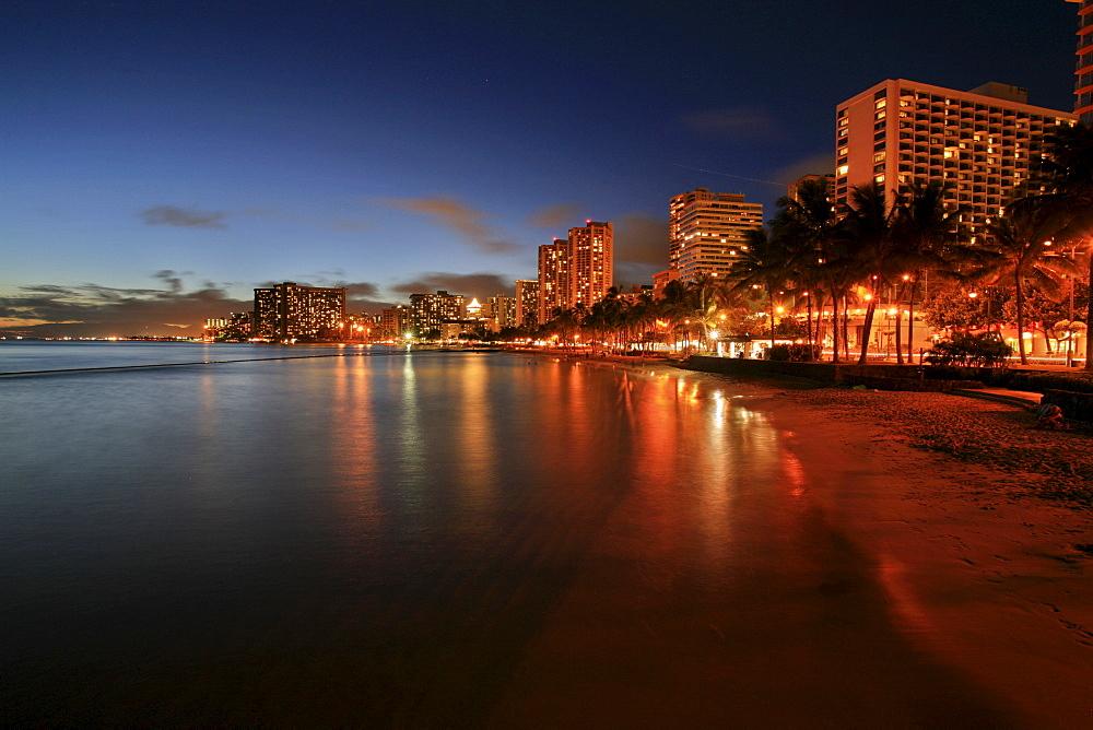 Beach and hotel complexes in Waikiki at dusk, O'ahu Island, Hawaii, USA