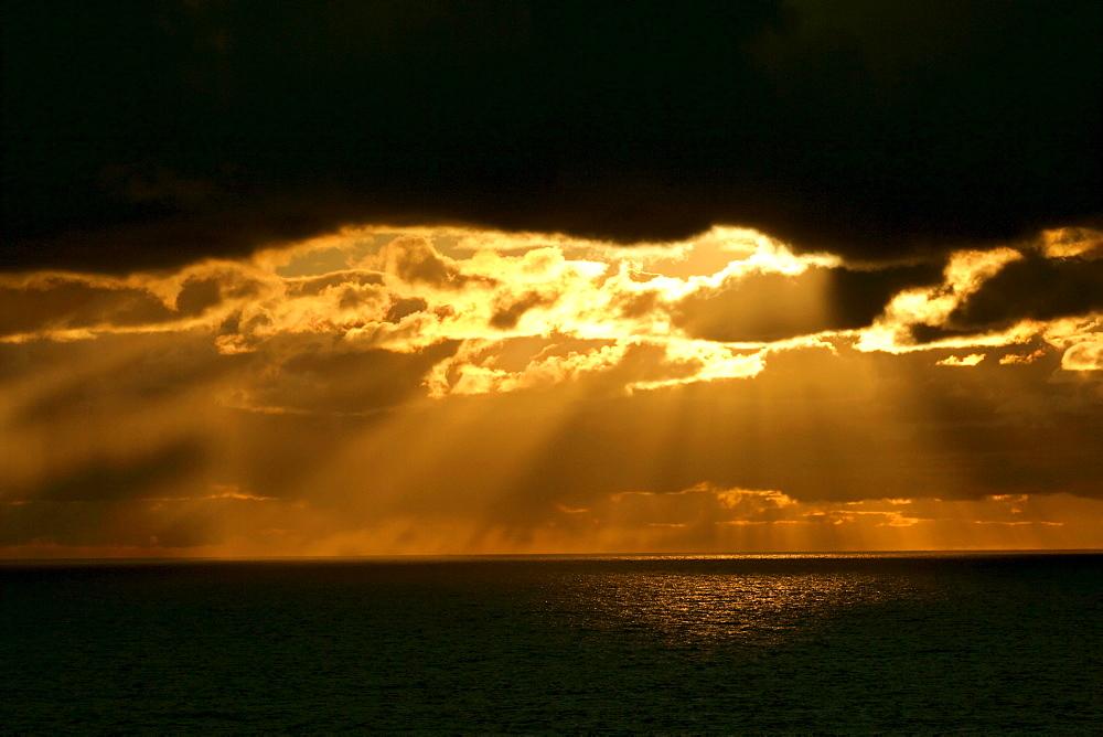 Seascape, spectacular sunbeams, rays of sunlight breaking through heavy cloud, Eshaness, Northmavine, North Mainland, Shetland Isles, Scotland, UK