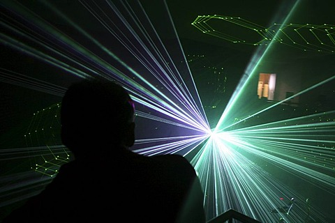 A man looks into the light of a laser during a presentation